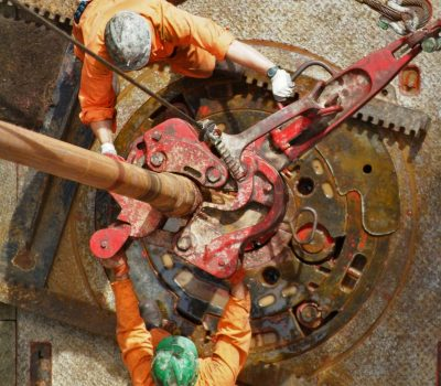 An elevated view of drill operators working on the drilling floor on an oil rig.